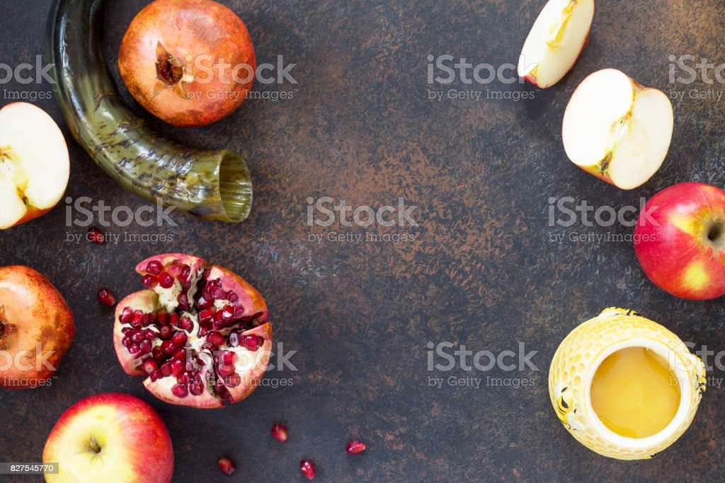 The concept of Rosh hashanah (Jewish New Year). Traditional holiday symbols - shofar, honey, apple and pomegranate on a stone or slate background. Flat lay, top view. stock photo