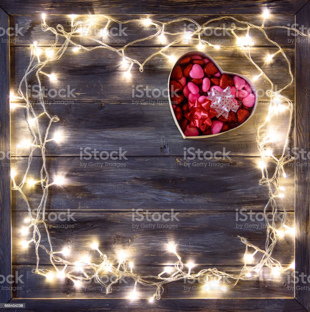 The concept of Valentine's Day with a garland and gift box in the shape heart on wooden background. stock photo