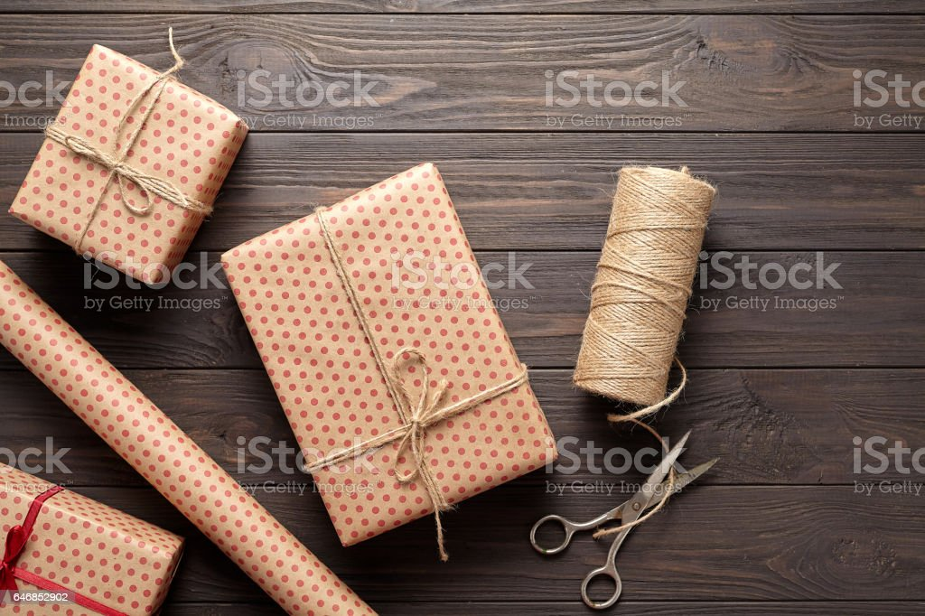 The concept of wrapping gifts in rustic style on birthday or holidays. Dark wooden background. Flat lay. stock photo