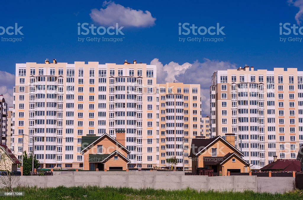 The construction of large apartment buildings displaces small ho stock photo