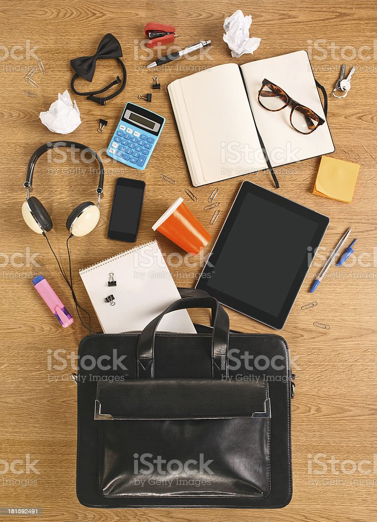 The contents of business briefcase on a wooden desk. royalty-free stock photo
