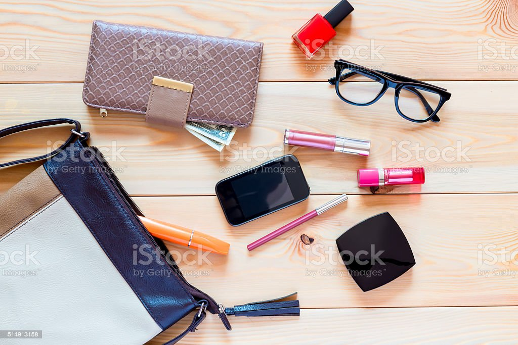 the contents of women's handbags are scattered on the floor stock photo
