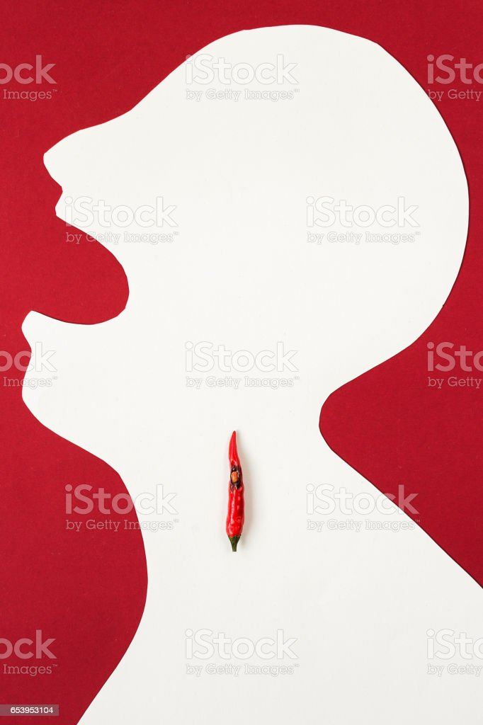 the contour of the person cut from white paper on a red background with an open mouth and hot red pepper lying inside him. cold concept, sore throat, burning in a throat, top view, flat lay stock photo
