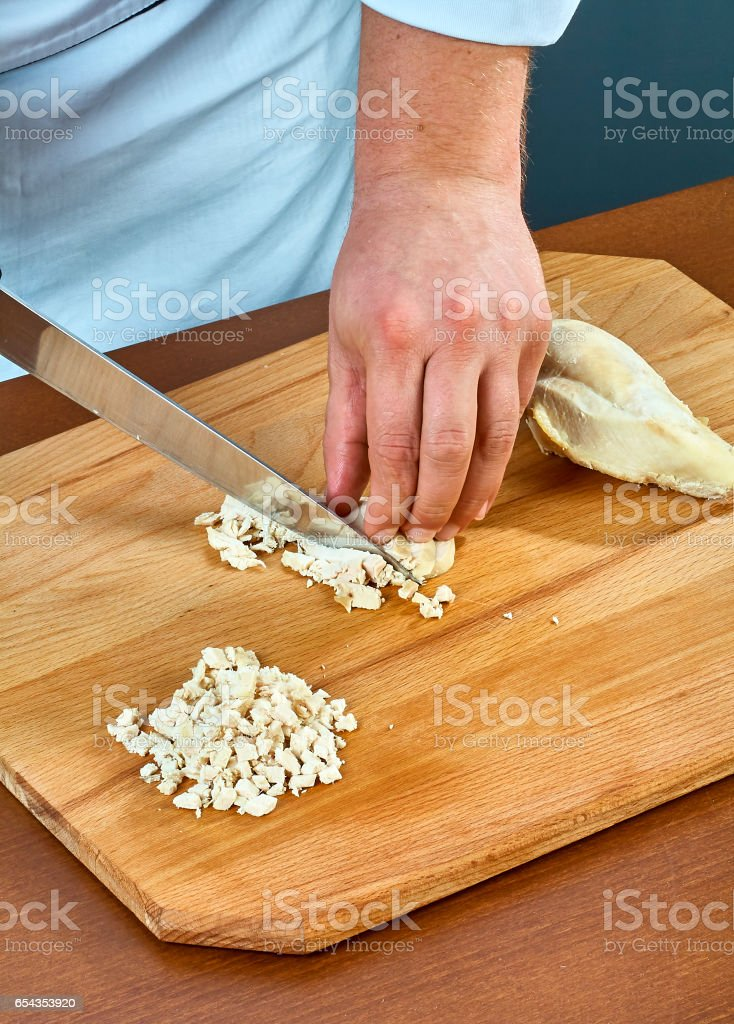 The cook cuts boiled chicken meat to prepare a jellied full collection of culinary recipes stock photo