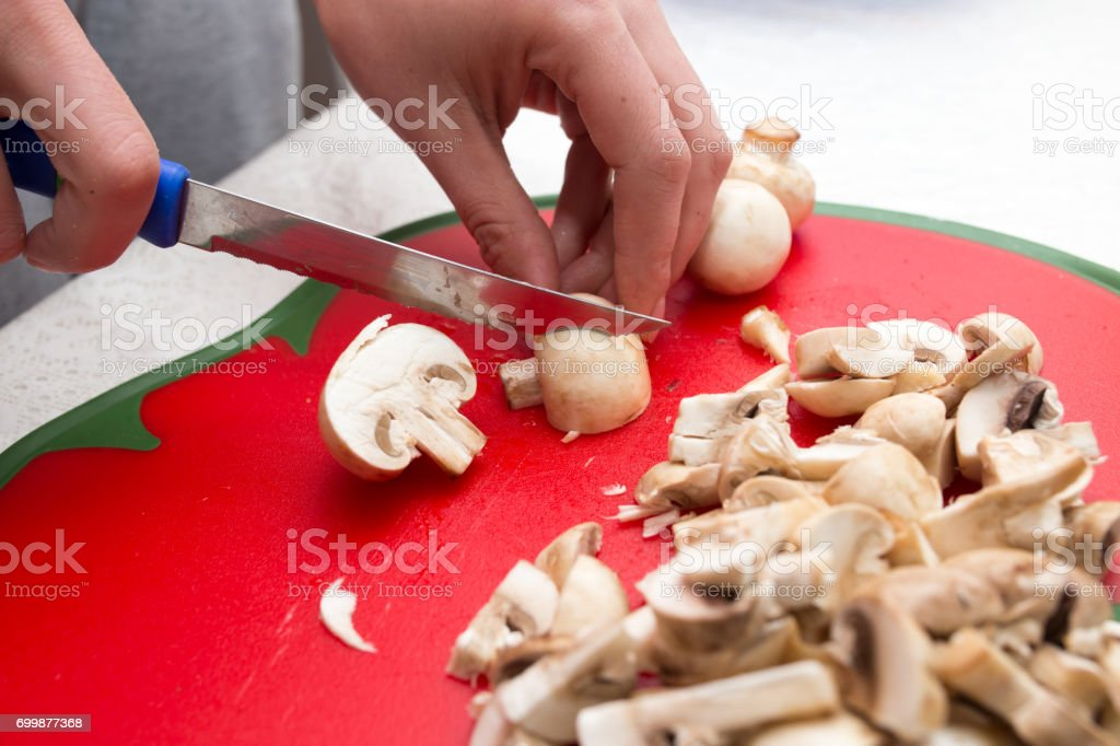 The cook cuts mushrooms with a knife stock photo