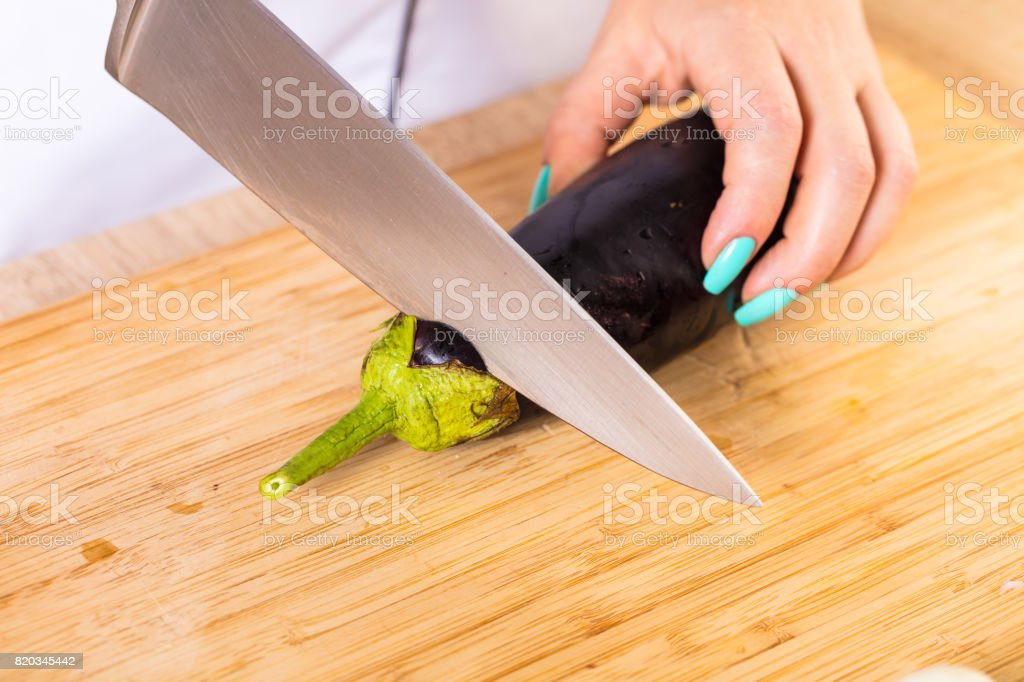 The cook cuts the eggplant stock photo