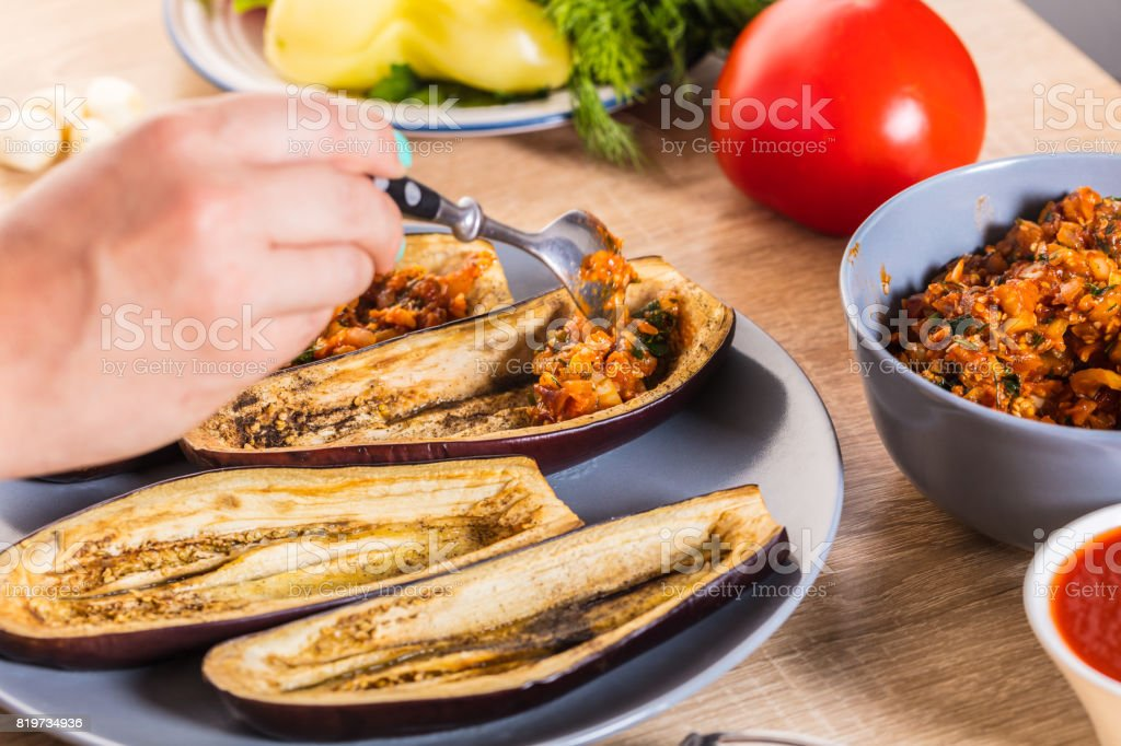 The cook fills the eggplant stock photo