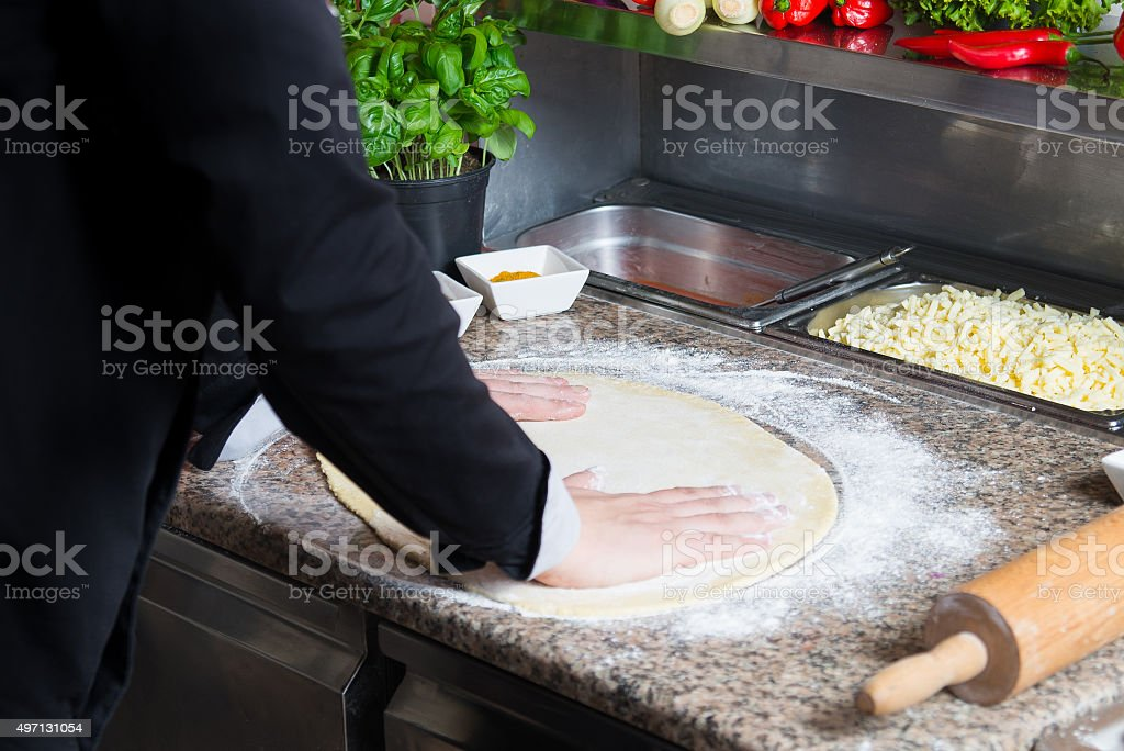 The cook prepares pizza. Smoothing the dough. stock photo