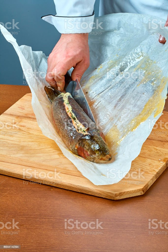 The cook wraps the fish in a paper for baking a full collection of food recipes stock photo