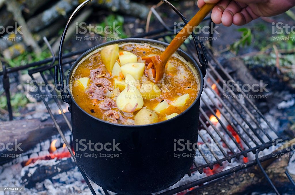 The cooking of soup on the fire stock photo
