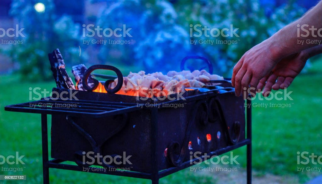The cook's hands are twisted skewers on the grill stock photo