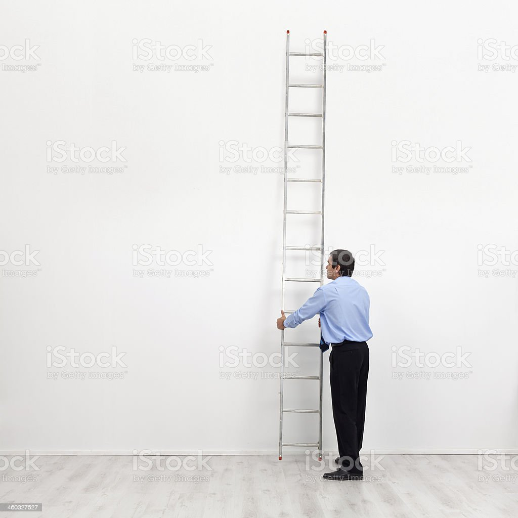 The corporate ladder - businessman begins to climb stock photo