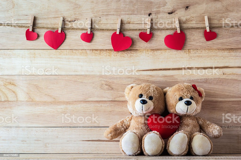 The couple Teddy bear holding a heart-shaped pillow stock photo