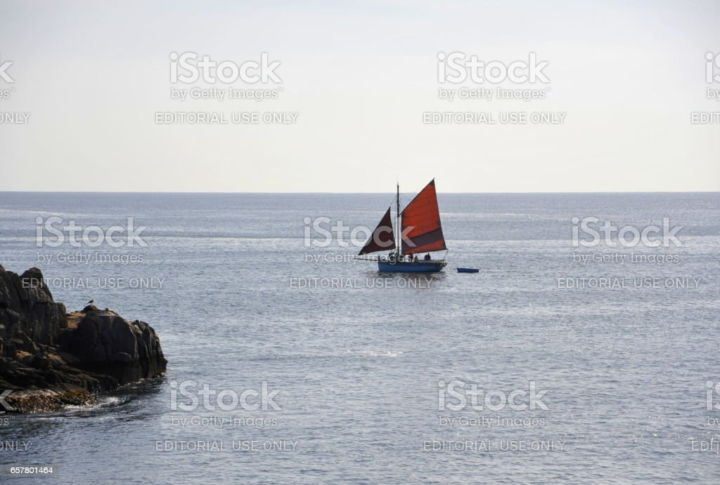 The crew of the 'Hope' leave Meule harbour, Ile d'Yeu, France. Here against a blue sky and sea. stock photo
