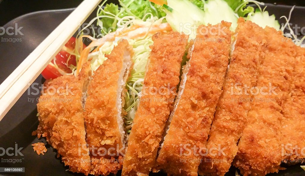 the crispy fried pork with vegetable in black plate, tonkatsu , stock photo