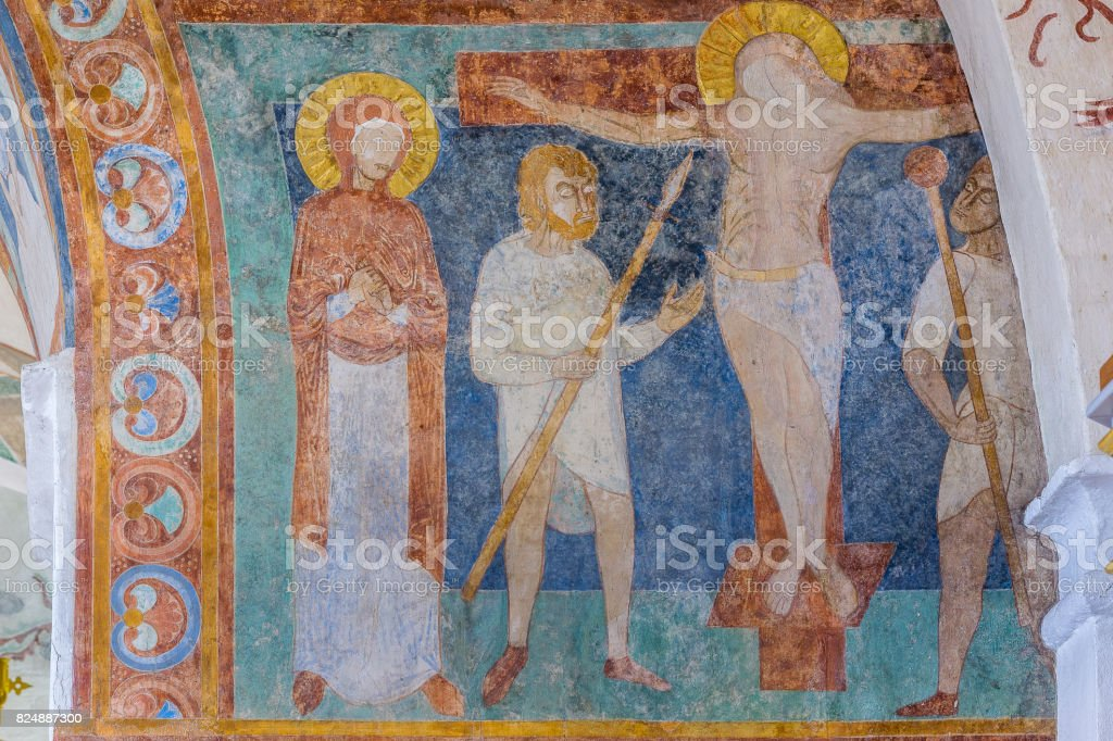 The crucifixion, a medieval romanesque fresco in blue stock photo