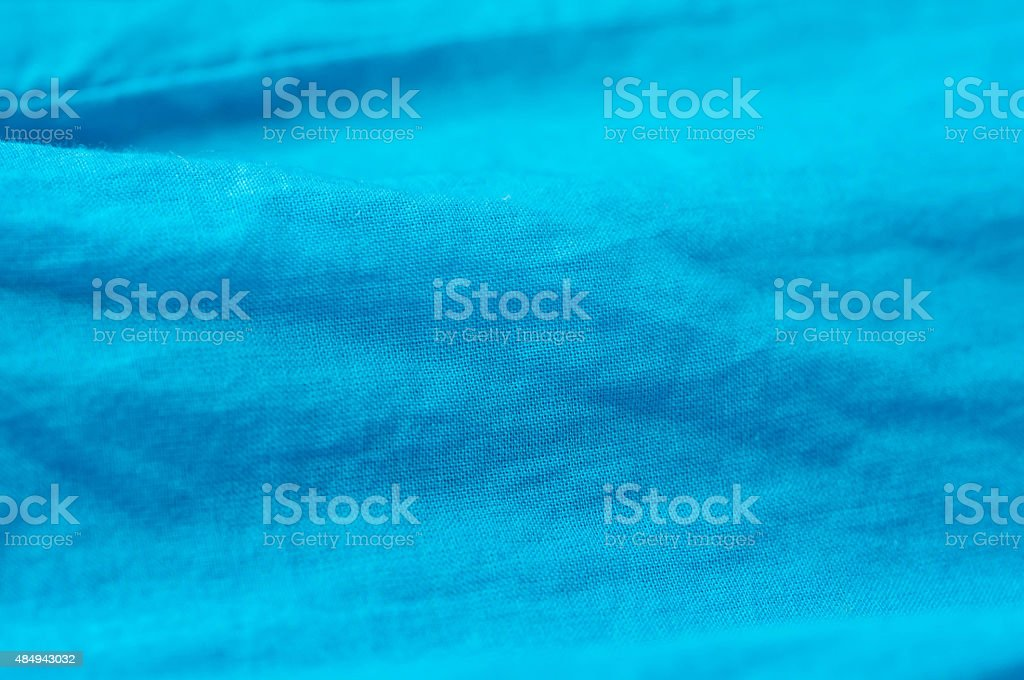 The crumpled textile background of turquoise color stock photo