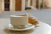 The cup of cappuccino with croissant on the street how background.