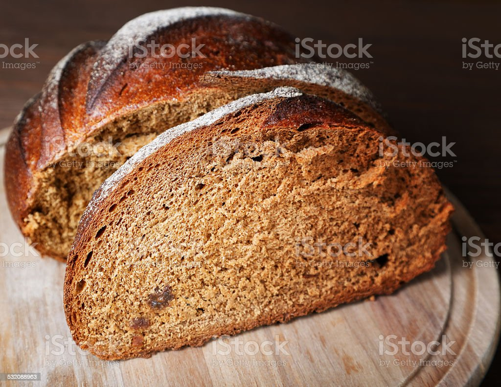 The cut black bread on a wooden table stock photo