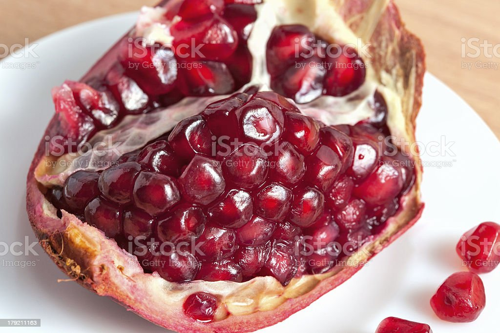 The cut pomegranate and grains on a plate royalty-free stock photo