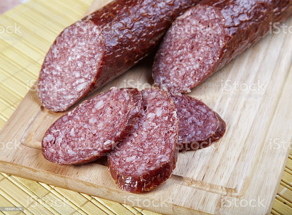 The cut smoked sausage on a wooden board royalty-free stock photo