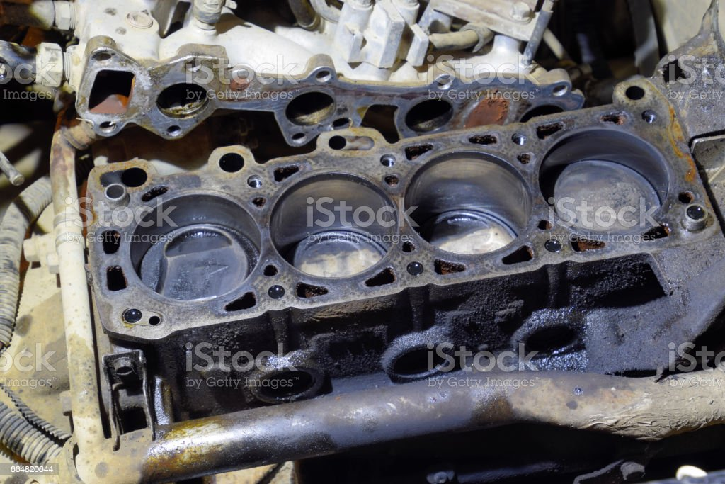 The cylinder block of the four-cylinder engine. Disassembled motor vehicle for repair. Parts in engine oil. Car engine repair in the service stock photo