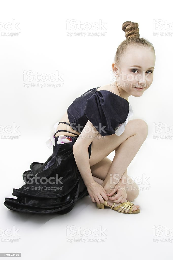The dancing girl has sat down to clasp a shoe stock photo