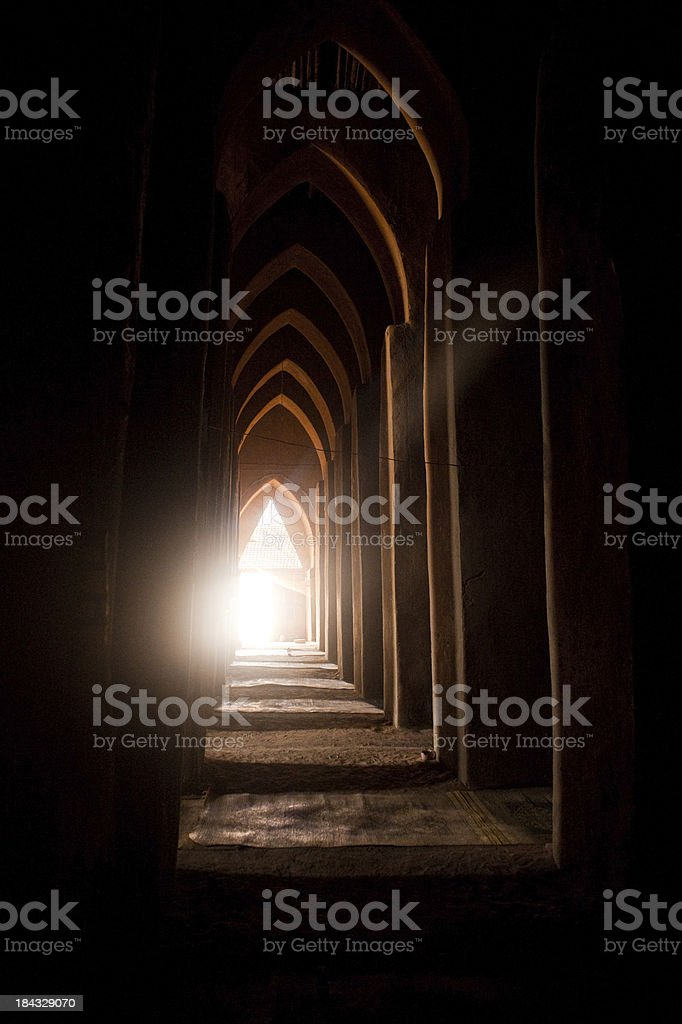 The dark interior of a loam mosque with bright exit stock photo