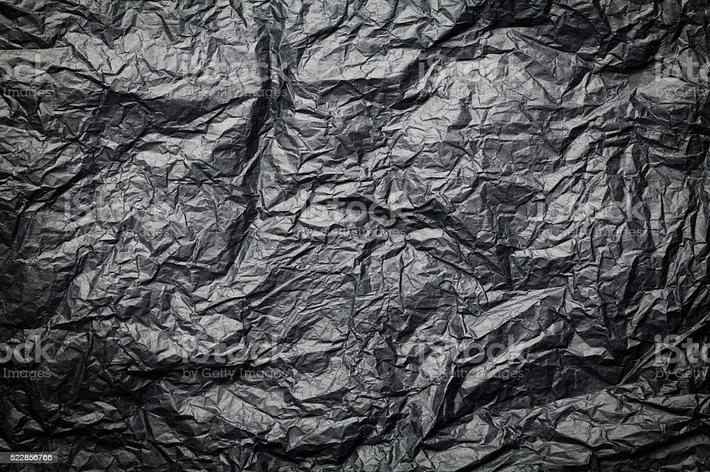 The dark texture of crumpled paper, black background stock photo