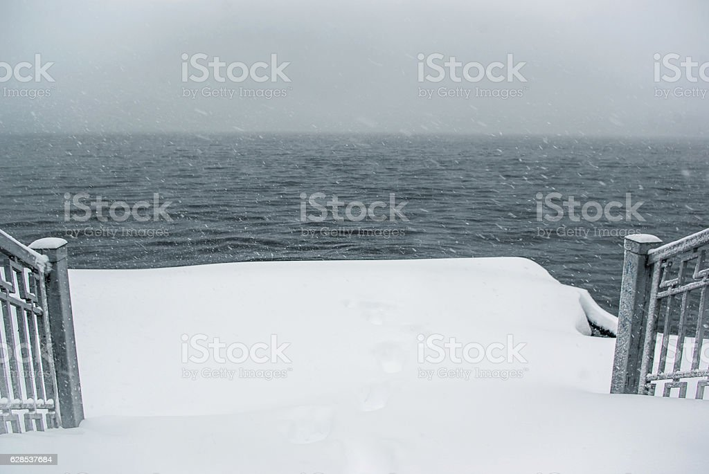 The dark water of the lake during a snowfall stock photo
