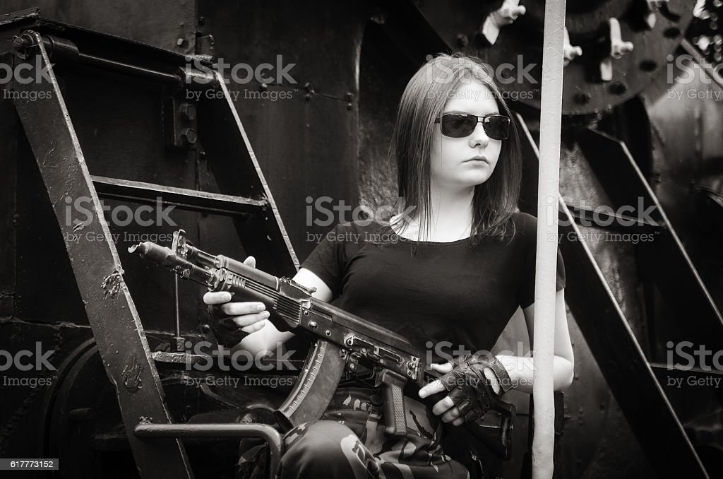 The dark-haired girl with a gun stock photo