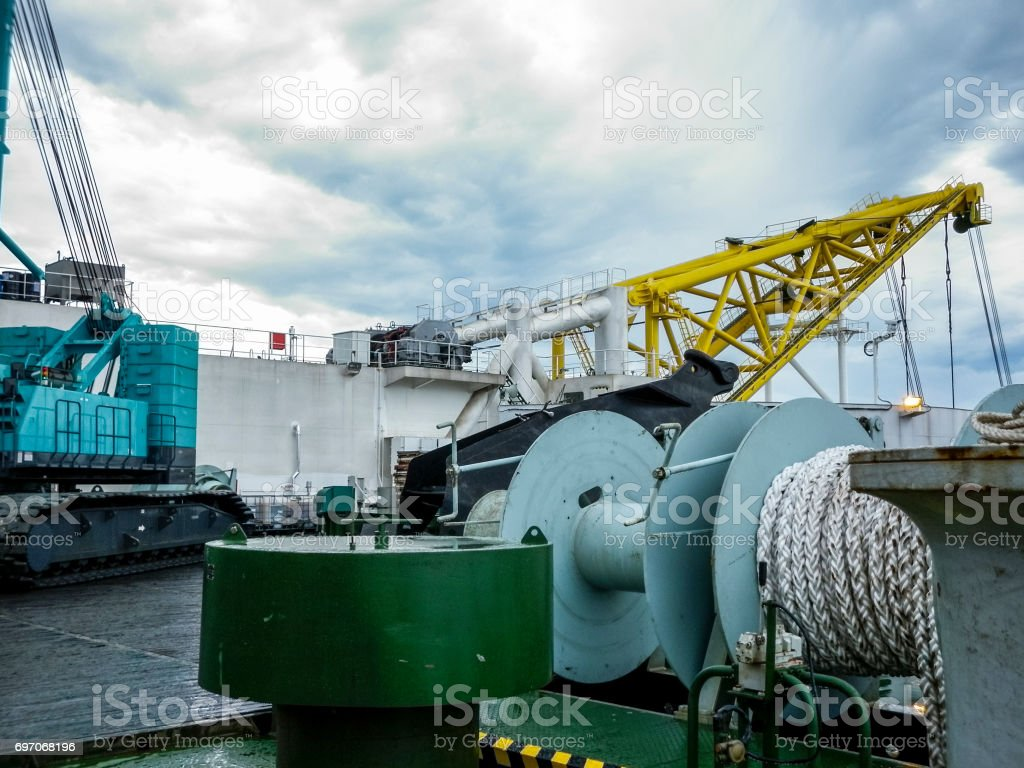The deck of the pipe-lay vessel. Cable winch and boom for pipes. The submersible on deck. stock photo