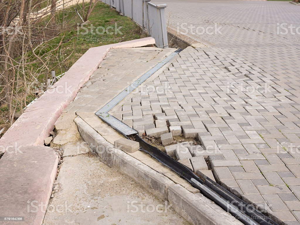 The destruction of the pedestrian walkway of pavers fixed concrete stock photo
