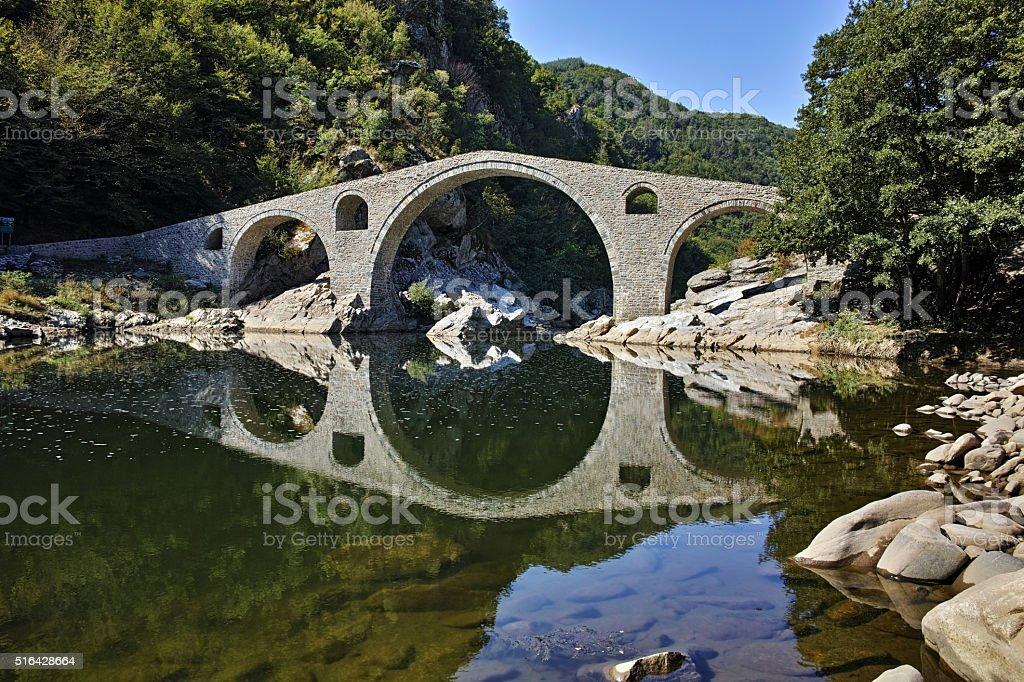 The Devil's Bridge and Rhodopes mountain in Arda river, Bulgaria stock photo