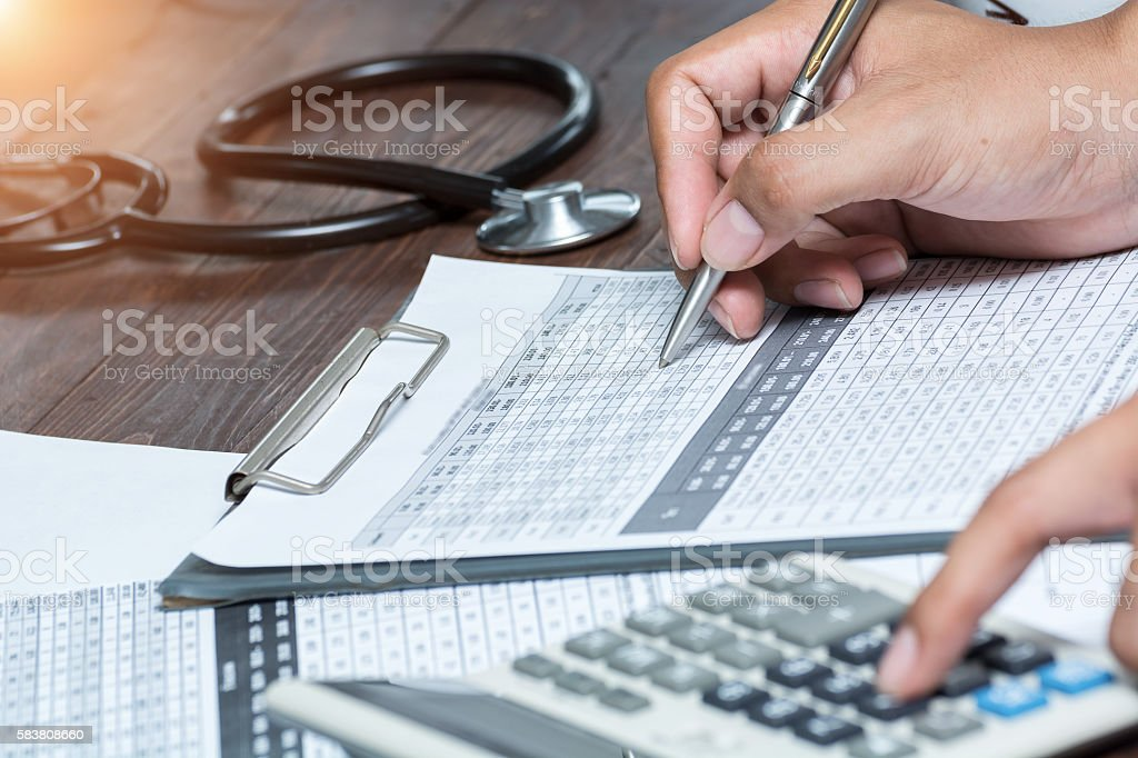 The doctor notes the healthcare professional calculator. stock photo