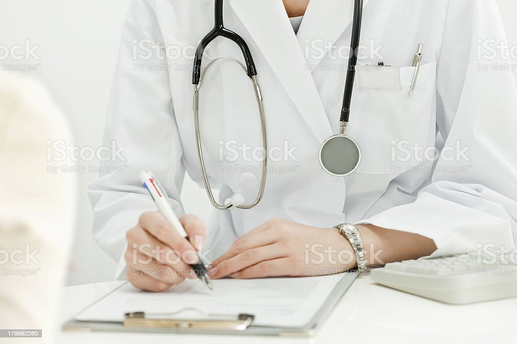 The doctor who fills out a medical record stock photo