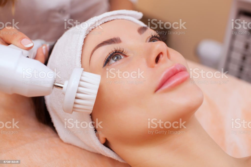 The doctor-cosmetologist makes the apparatus a procedure of Hardware face cleaning with a soft rotating brush of a beautiful, young woman stock photo