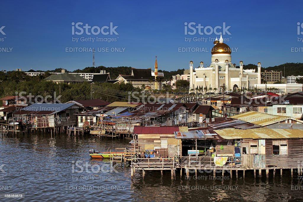 The dome of Brunei's Mosque contrasts with water village stock photo