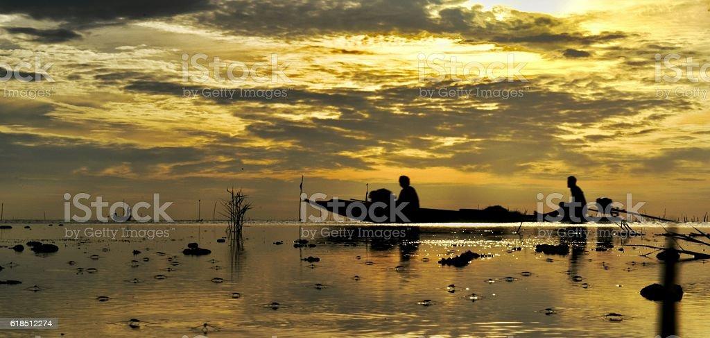 The drift boat on the sea with glodsky sunrise backgrund stock photo