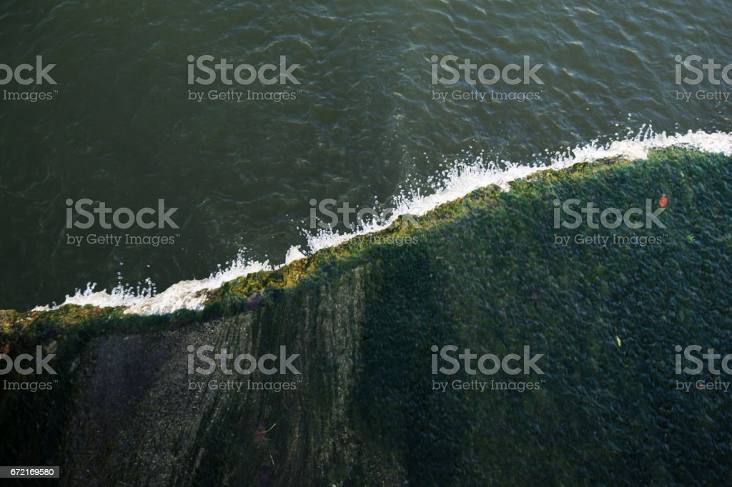 The edge of man-made waterfall from above. stock photo