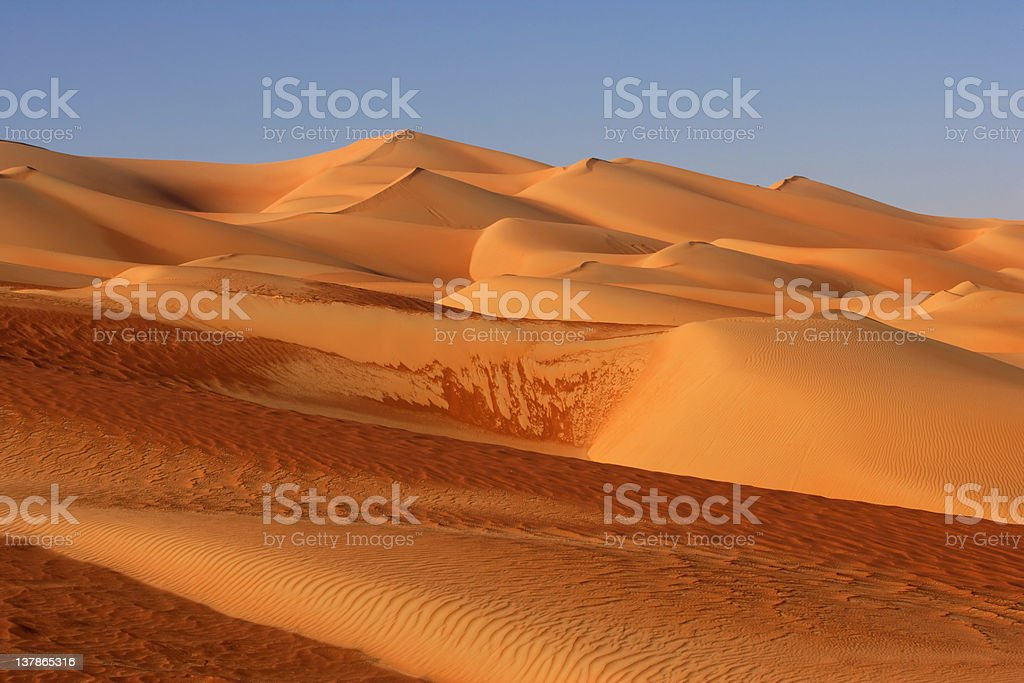 The Empty Quarter Dunes during the day with a clear blue sky stock photo