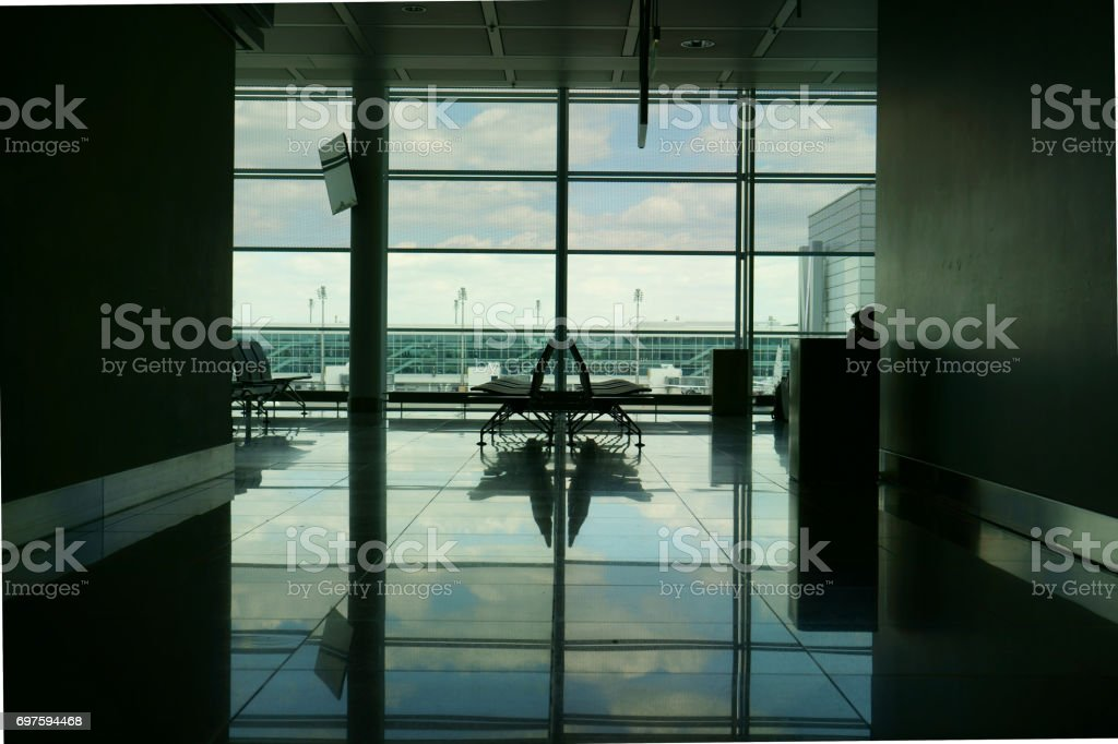 The empty seat near by the airport windows with the reflection of sky and cloud at the departure lounge stock photo