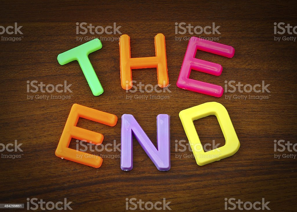 The end in colorful toy letters on wood background royalty-free stock photo