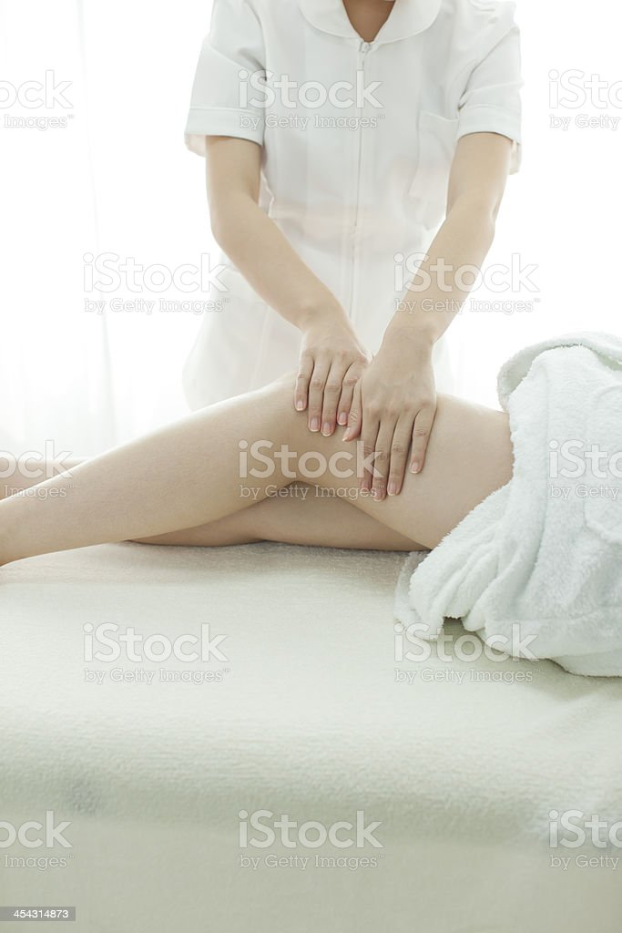 The esthetician who massages a leg royalty-free stock photo