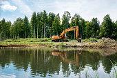 The excavator against a summer landscape