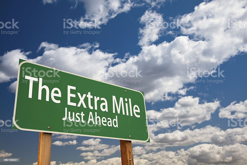 The Extra Mile Just Ahead Green Road Sign Over Sky stock photo