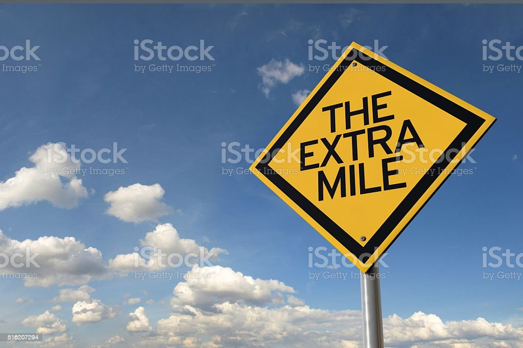 The extra mile yellow highway road sign stock photo