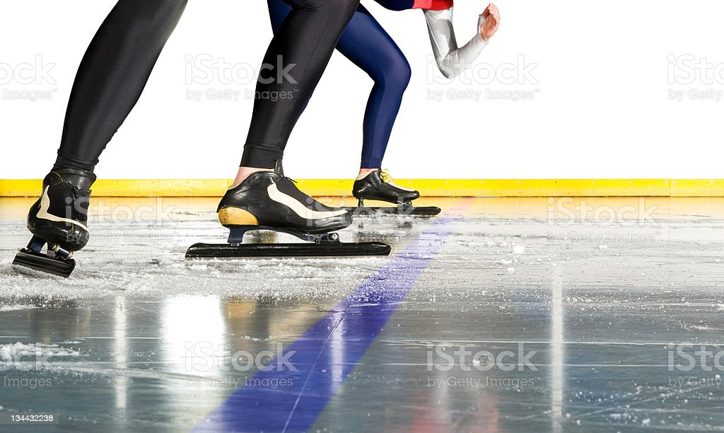 The feet and legs of speed skaters poised at the start line stock photo