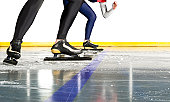 The feet and legs of speed skaters poised at the start line