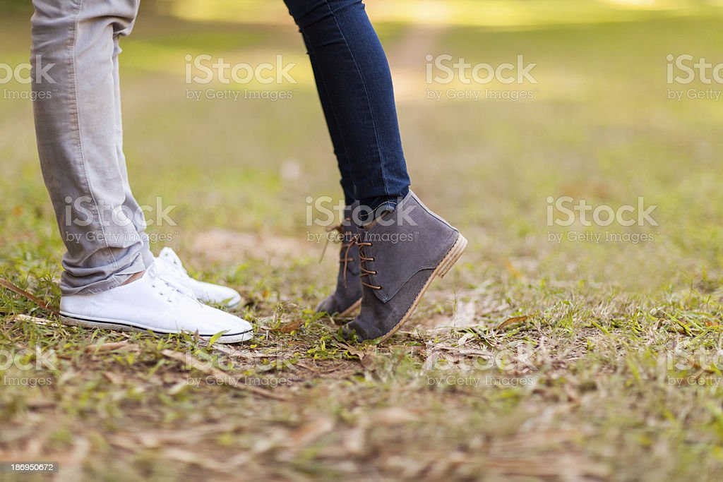 The feet of a teenage couple kissing outside stock photo